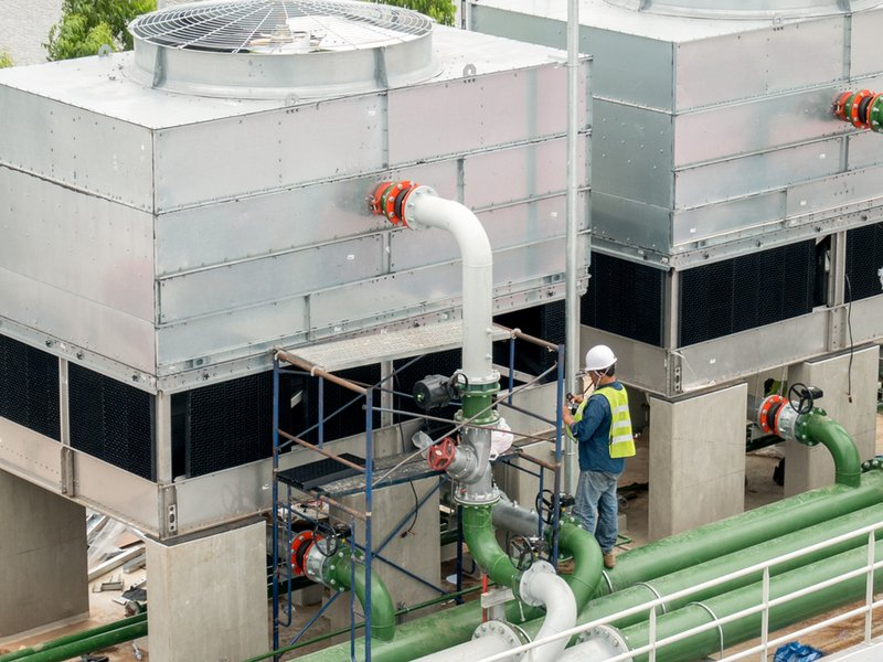Man working on a huge rooftop chiller system
