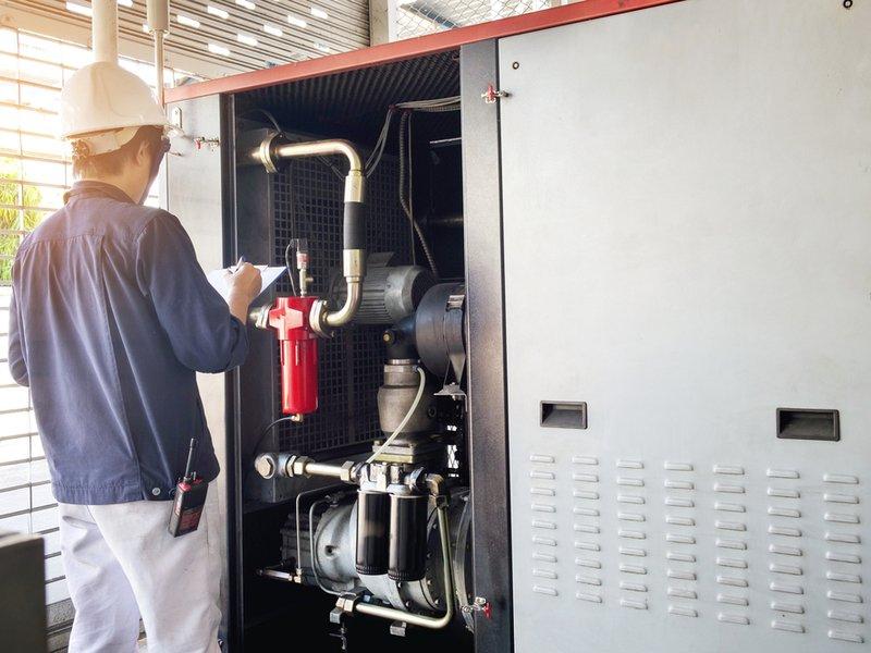 Man examining industrial air conditioning system