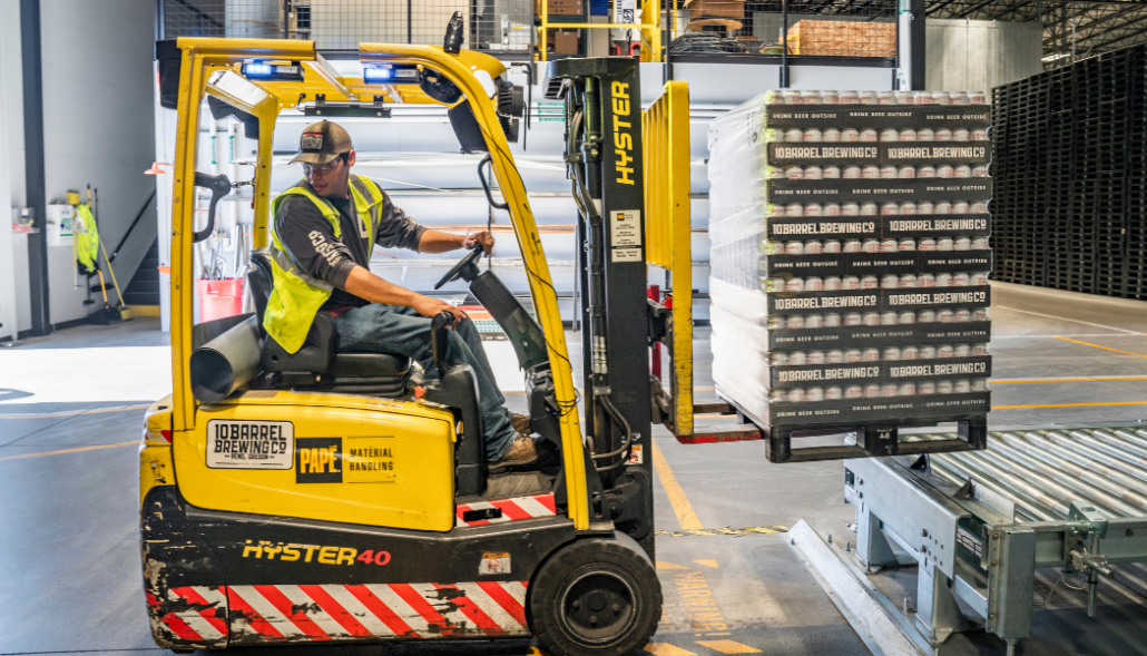 Loading dock worker on forklift with open doors
